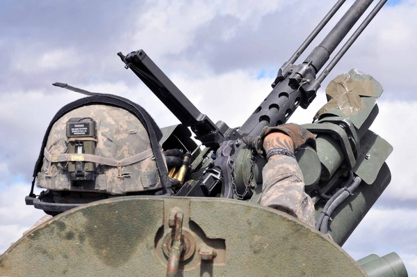 A U.S. Soldier with the 5th Battalion, 20th Infantry Regiment, 3rd Stryker Brigade Combat Team, 2nd Infantry Division, loads his .50-caliber machine gun during a joint platoon exercise at the Yakima Training Center, Wash., Sept. 16, 2013. Rising Thunder is a U.S. Army-hosted exercise designed to build interoperability between I Corps, the 7th Infantry Division and the Japan Ground Self-Defense Force.  (U.S. Army photo by Sgt. Austan Owen/Released)