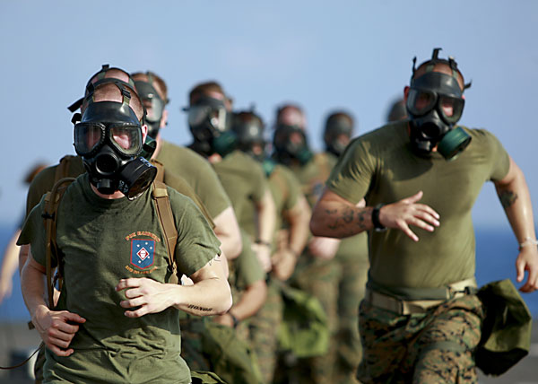02/21/2010 - U.S. Marines assigned to the 31st Marine Expeditionary Unit run while wearing gas masks during physical training on the flight deck of USS Harpers Ferry (LSD 49) Feb. 21, 2010, while under way in the South China Sea. Harpers Ferry is a part of the forward-deployed Essex Amphibious Ready Group and is conducting a spring patrol to the western Pacific Ocean. (DoD photo by Chief Gas Turbine System Technician (Mechanical) Joel Monsalud, U.S. Navy/Released)