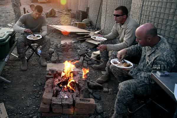 Soldiers eat their Thanksgiving meal on Combat Outpost Cherkatah in the Khowst province of Afghanistan, Nov. 26, 2009. The Soldiers are deployed with Company D, 3rd Battalion, 509th Infantry Regiment.  Photo by Staff Sergeant Andrew Smith.