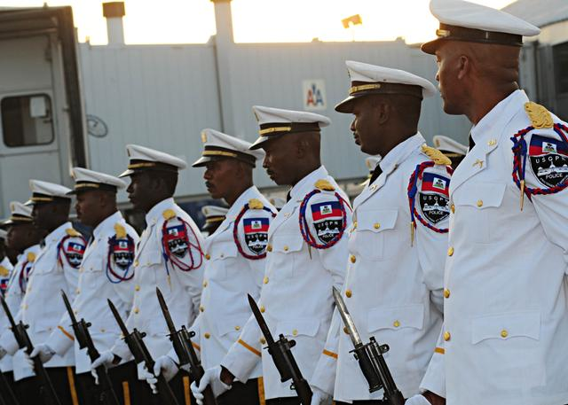02/20/2010 - Members of the Haitian National Police Force's marching band stand at parade rest while awaiting the start of a reception for a Chilean flight crew at Toussaint L'Ouverture International Airport in Port-au-Prince, Haiti, Feb. 20, 2010. The U.S. military has returned control of the airport to the Haitian government more than a month after the earthquake that struck the region Jan. 12, 2010. (DoD photo by Mass Communication Specialist 2nd Class Kim Williams, U.S. Navy/Released)
